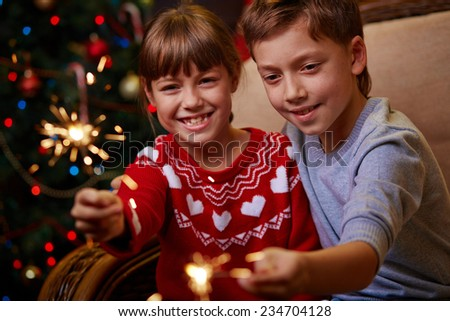Cute siblings with Bengal lights celebrating Christmas - stock photo
