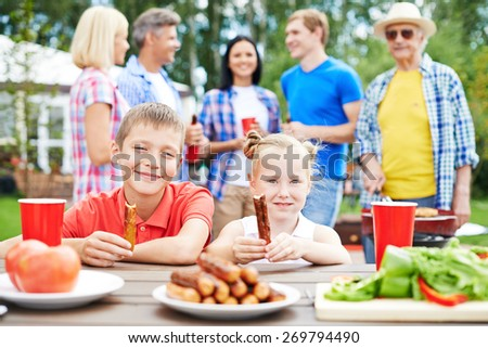 Cute siblings with sausages eating outdoors with their parents on background - stock photo