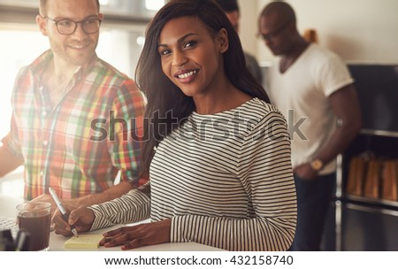 Cute single African American woman in striped shirt writing notes on desk next to man at work - stock photo