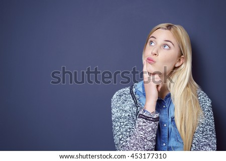 Cute single blond and blue eyed young woman in sweater with curious expression and finger on lip while looking sideways over dark background with copy space - stock photo