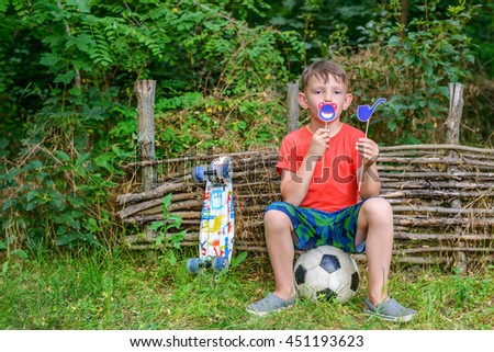 Cute single boy seated on soccer ball near compost pile holding toy pipe and joking symbols near his mouth