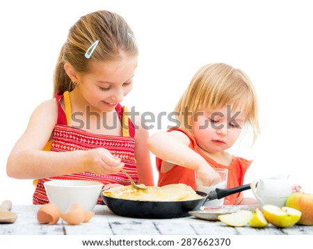 cute sisters cooking pancakes on kitchen isolated on a white background - stock photo