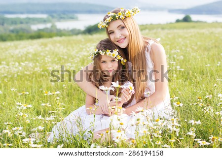 Cute sisters girls is playing at  green chamomile field with mountains view - stock photo