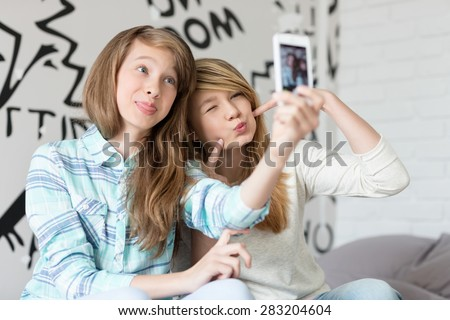 Cute sisters pouting while taking photos with smart phone at home - stock photo