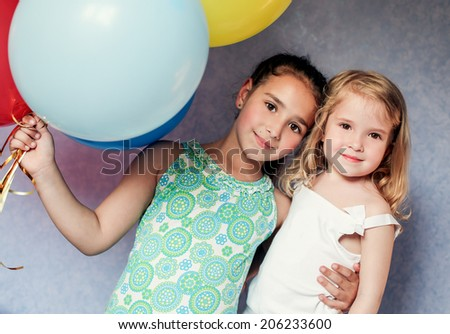 cute sisters with colorful balloons house - stock photo