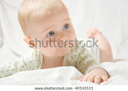 Cute six month old baby laying on stomach and look around her on white sheet