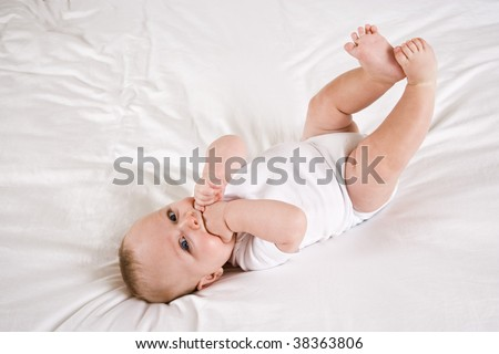 Cute six month old baby with lying down on white bed