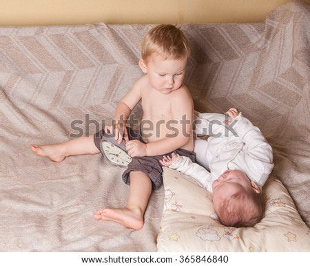 cute six months old baby and toddler boy with an alarm clock. Two children playing in bed - stock photo