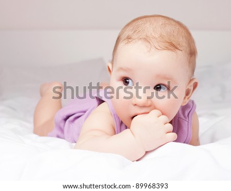 cute six months old baby lies in the bed at home and sucks his big finger - stock photo