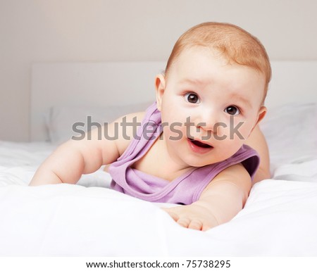 cute six months old baby on the bed at home