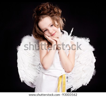 cute  six year old girl  dressed as a cupid with white wings, isolated against black studio background - stock photo