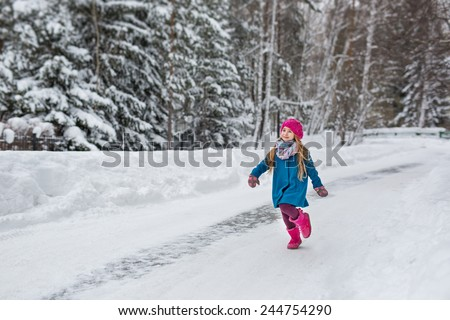 Cute six year old girl dressed in a blue coat and a pink hat and boots, fun runs through the winter forest - stock photo