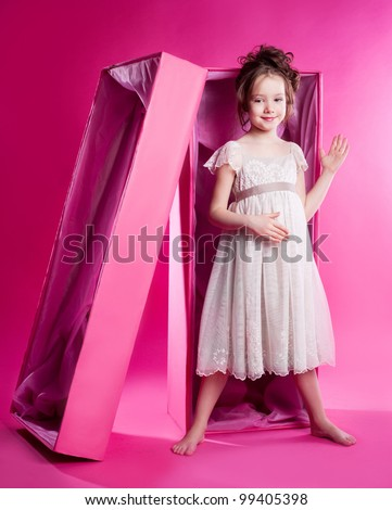 cute six year old girl photographed as an alive doll in the pink box,  against pink studio background - stock photo