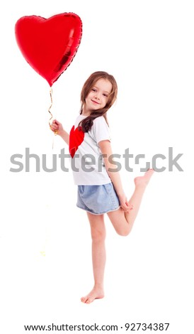 cute six year old girl wearing a T-shirt with a big red heart, isolated against white background