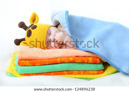 cute sleeping baby boy in funny hand made giraffe hat, beautiful kid dozing on pile of colorful towels with blue plaid, studio shot - stock photo