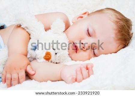 Cute sleeping child with teddy bear - stock photo