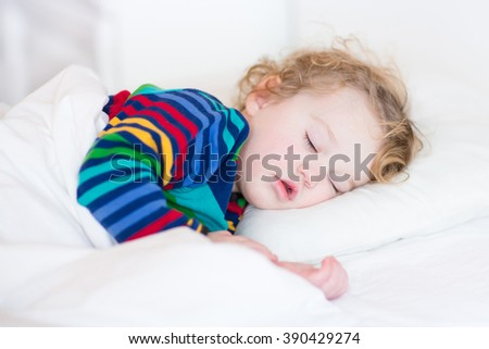 Cute sleeping toddler girl in a white bed - stock photo