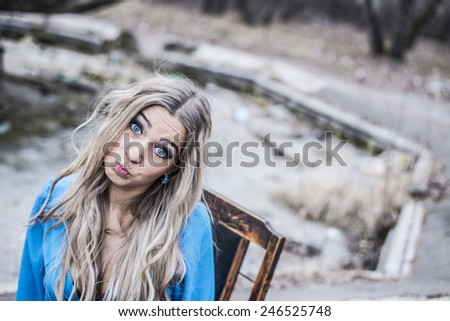"""Cute slim female with long blond curly hair looking at camera Outdoor on autumn park background portrait of young pretty girl kidding and squinting Woman making funny face known as """"fish-face & quot  - stock photo"""