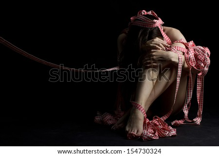 Cute slim girl tied with rope on black background - stock photo