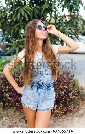 Cute slim tanned girl standing near tree. She wears white t-shirt, denim shorts and black sunglasses. She has long dark straight hair. She smiles and touches her sunglasses with her hand.  - stock photo