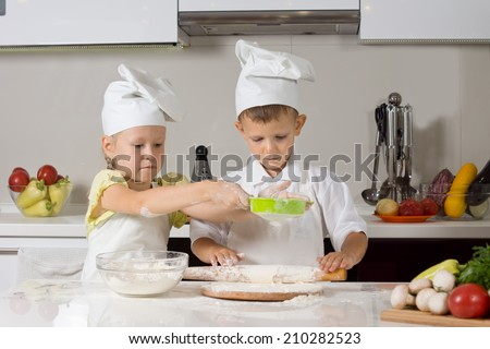 Cute small boy and girl wearing cooks uniforms baking together in the kitchen working a a team making and rolling out dough for pizza bases