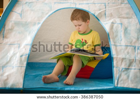 Cute small boy in a yellow t-shirt sitting inside a big  tent and reading a book. Kid with a book. pre-school readings at home, Activities with children indoors. Fairy tales for little ones. - stock photo