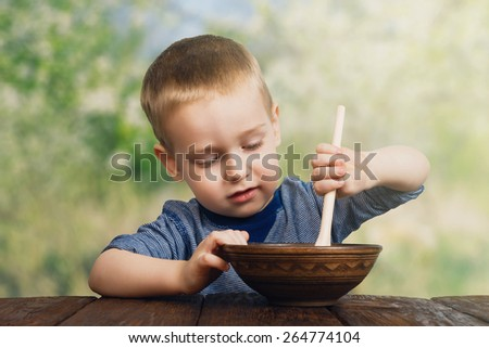 Cute small child boy eats his food from clay bowl with wooden spoon outdoors - stock photo