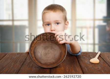 Cute small child boy sitting at wooden table shows empty plate - stock photo