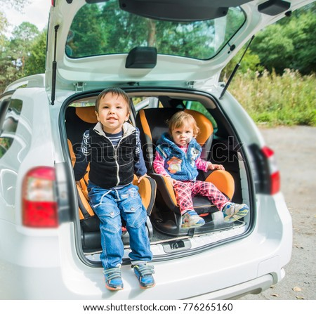 cute small children inside car seats in the car.Happy kids, adorable girl with her brother sitting together in modern car locked with safety belts enjoying family vacation trip on summer weekend