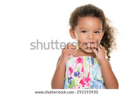 Cute small girl eating a cookie isolated on white - stock photo