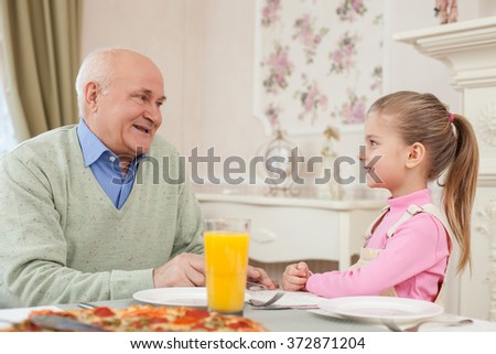Cute small girl is dining with her grandparent - stock photo