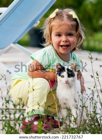 cute small girl is hug a cat, happy portrait with children and animal