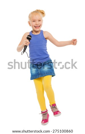 Cute small girl singing in microphone and dancing - stock photo