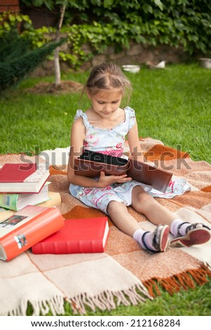 Cute small girl sitting on plaid and holding family photo album - stock photo