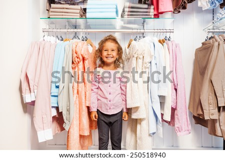 Cute small girl standing between clothes on hanger