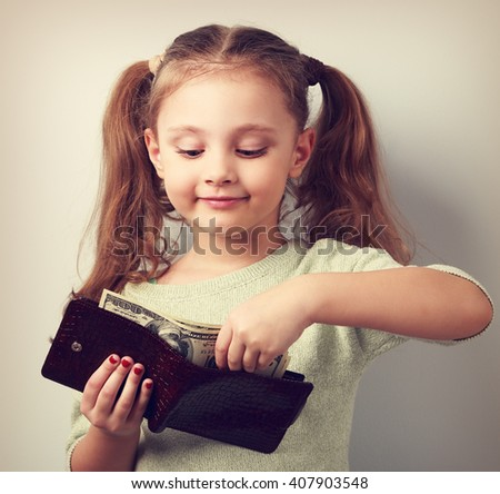 Cute small kid girl taking dollars from mother wallet and looking happy. Toned closeup portrait