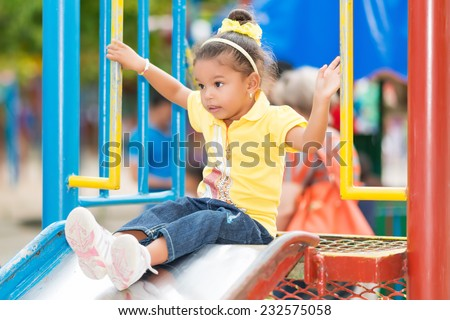 Cute small mixed race girl using a slide at a colorful playground - stock photo