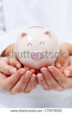 Cute small piggy bank in child hands - upheld by adult hands, financial education concept - stock photo