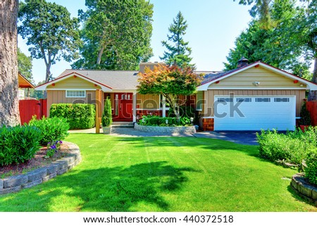 Cute small rambler house with red door and white garage door. Front garden with well kept lawn.