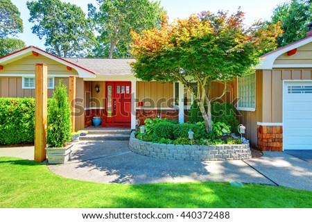 Cute small rambler house with red door and white trim.  View of concrete walkway with grass and flower bed. - stock photo