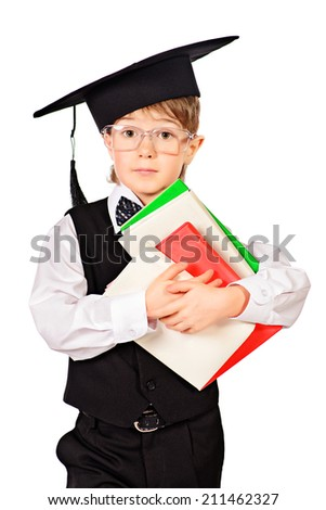 Cute smart boy in a suit and academic hat holding books. Educational concept. Isolated over white.