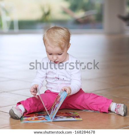 Cute smart little baby or toddler girl reading book sitting indoors on a tiles floor - stock photo
