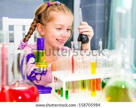 cute smiley little girl with flasks for chemistry - stock photo