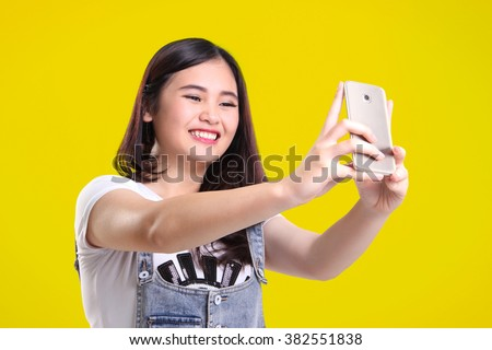 Cute smiling Asian teenage girl taking self shot photo with her phone camera, on bright yellow background - stock photo