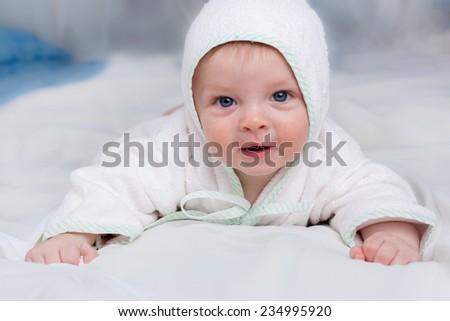 Cute smiling baby boy  lying on soft sofa in white bathrobe hood - stock photo