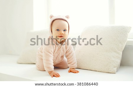 Cute smiling baby crawls in white room at home near window - stock photo
