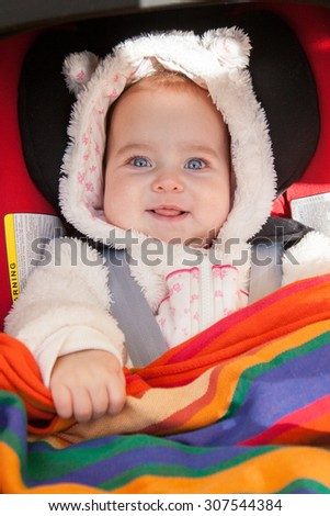 Cute smiling baby girl dressed in fur all-in-one with hood lying in car seat for infants. - stock photo