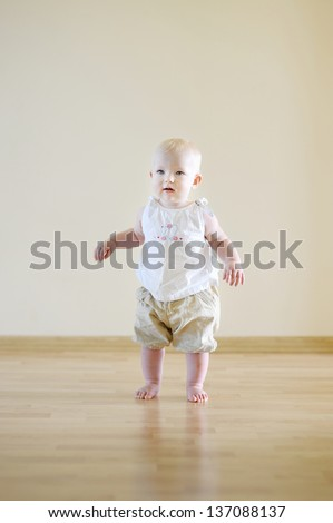 Cute smiling baby girl learning to walk
