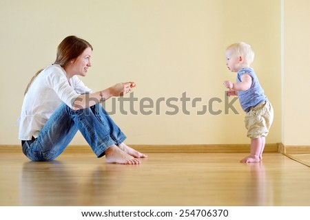 Cute smiling baby girl learning to walk - stock photo