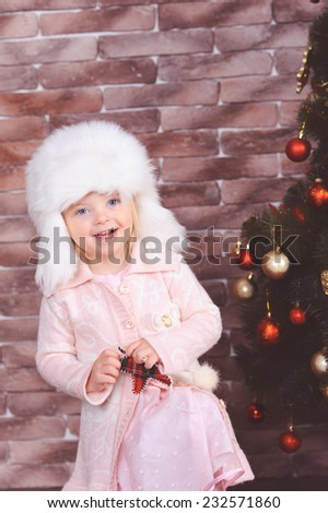Cute smiling baby girl wearing fur hat, playing near christmas tree in room - stock photo
